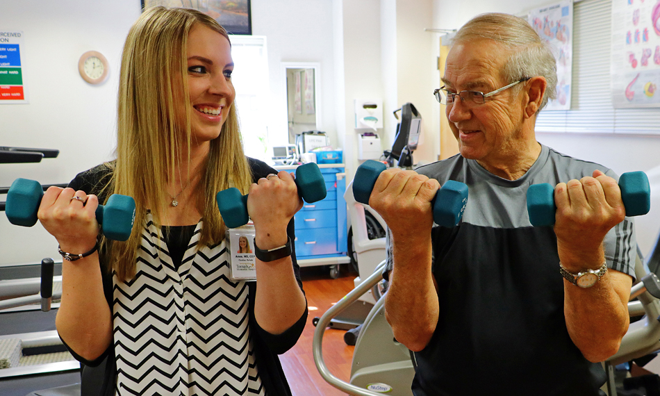 Cardiac Rehab trainer working with an older man, both using small dumbells in each hand