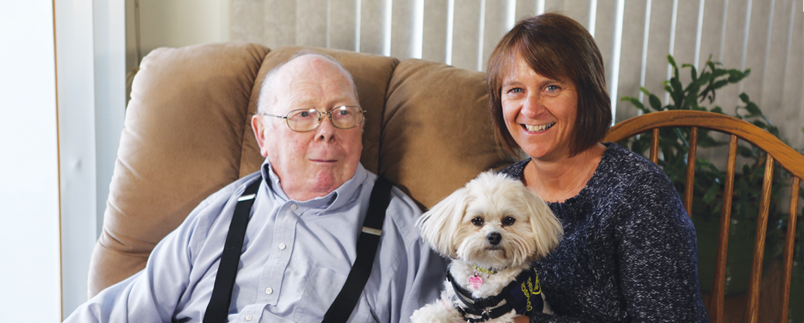 Hospice volunteer Teresa Hubert holding a dog and sitting next to a geriatric man
