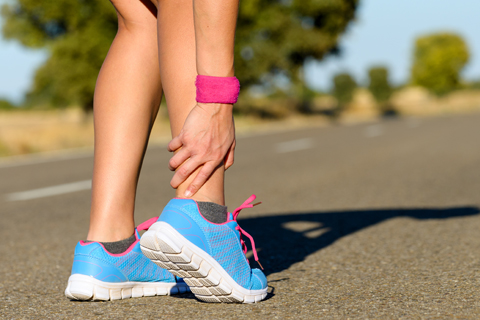 Lower portion of a woman in running shoes grasping her ankle